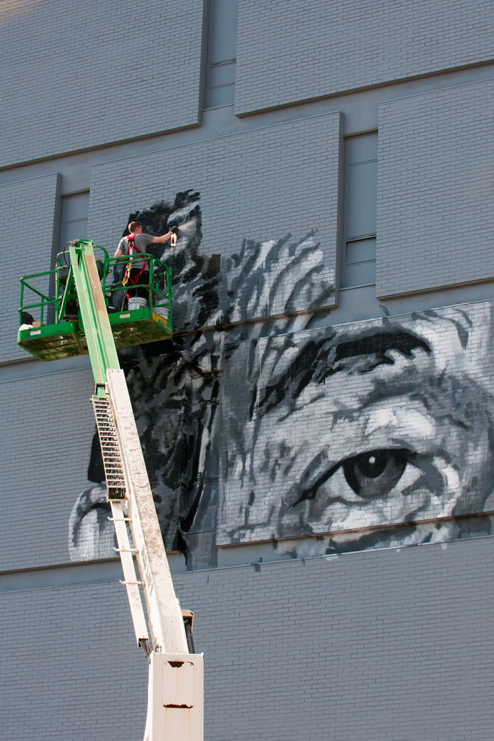 ECB at work on his six-story tall mural for Open Walls Baltimore