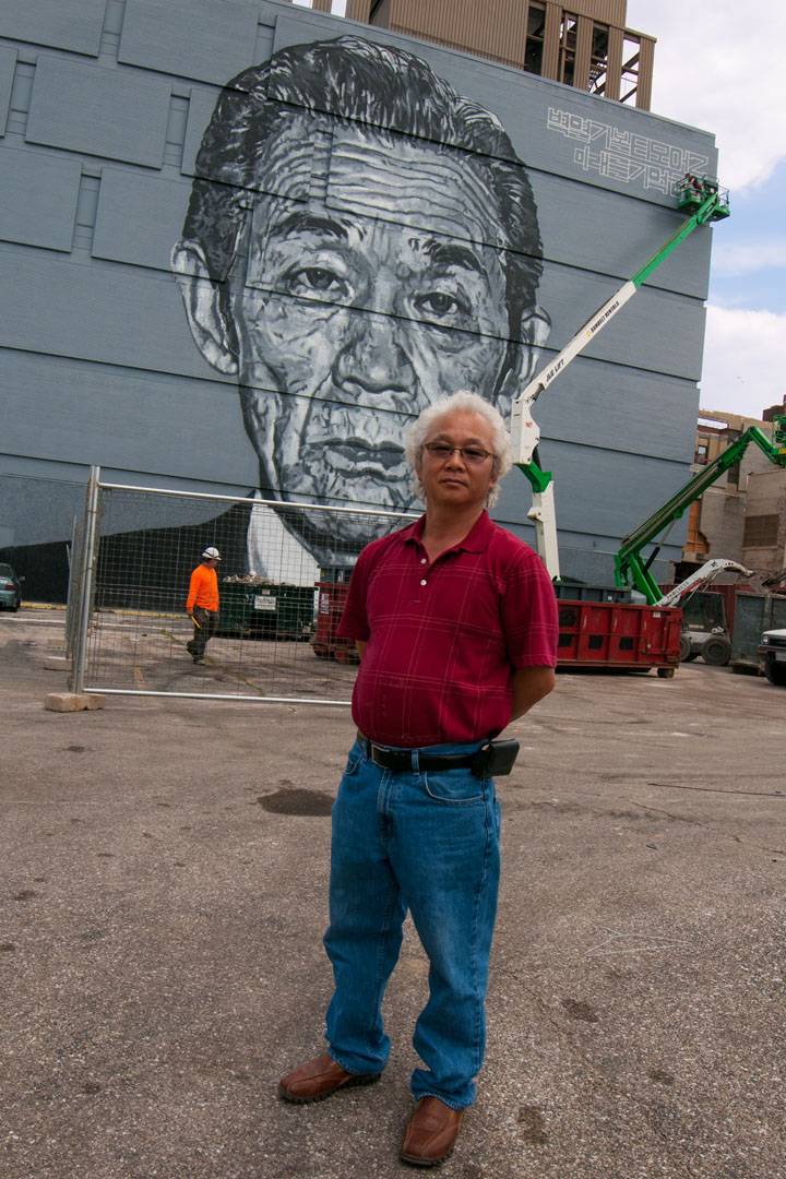 Mr. Kim stands before ECB's mural of his late father, a beloved