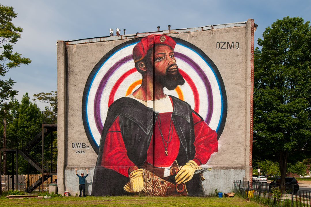 Finito - Ozmo stands beneath his mural at Open Walls Baltimore 2