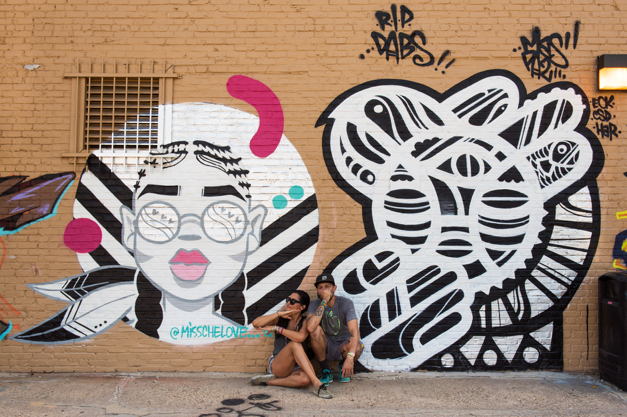 Miss Chelove and Mas Paz pose beneath their murals