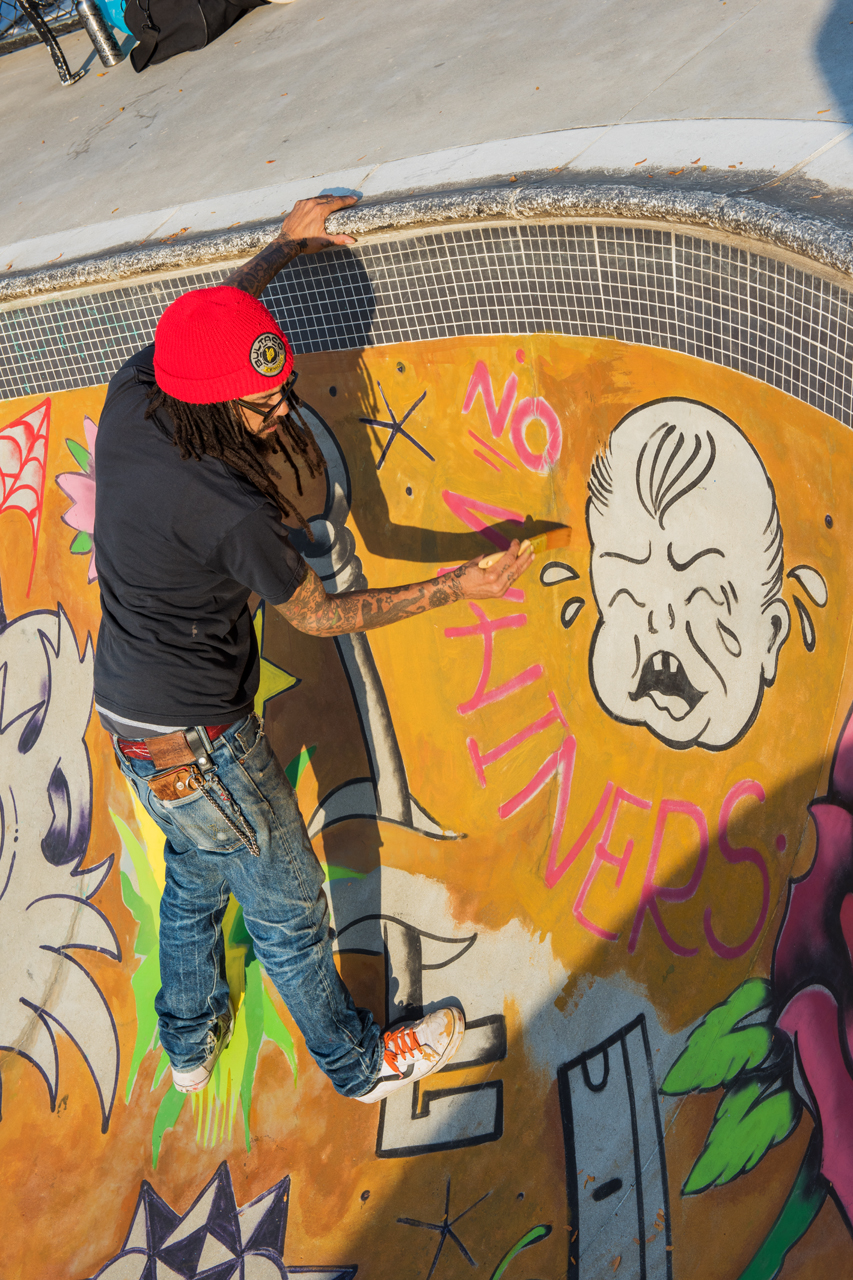 Adam painting on the mural's background color