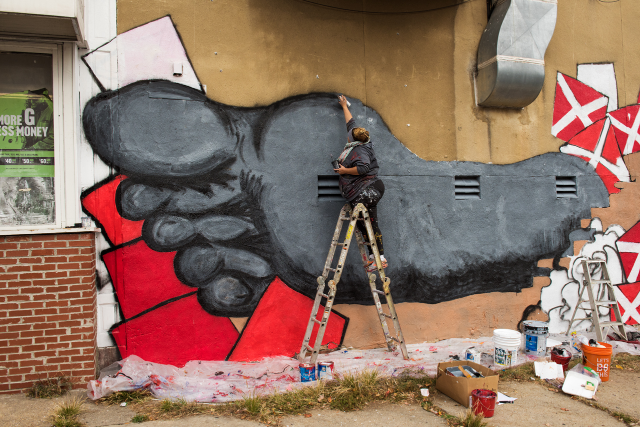 Ali Duggan at work on her mural in Baltimore's Harlem Park neighborhood