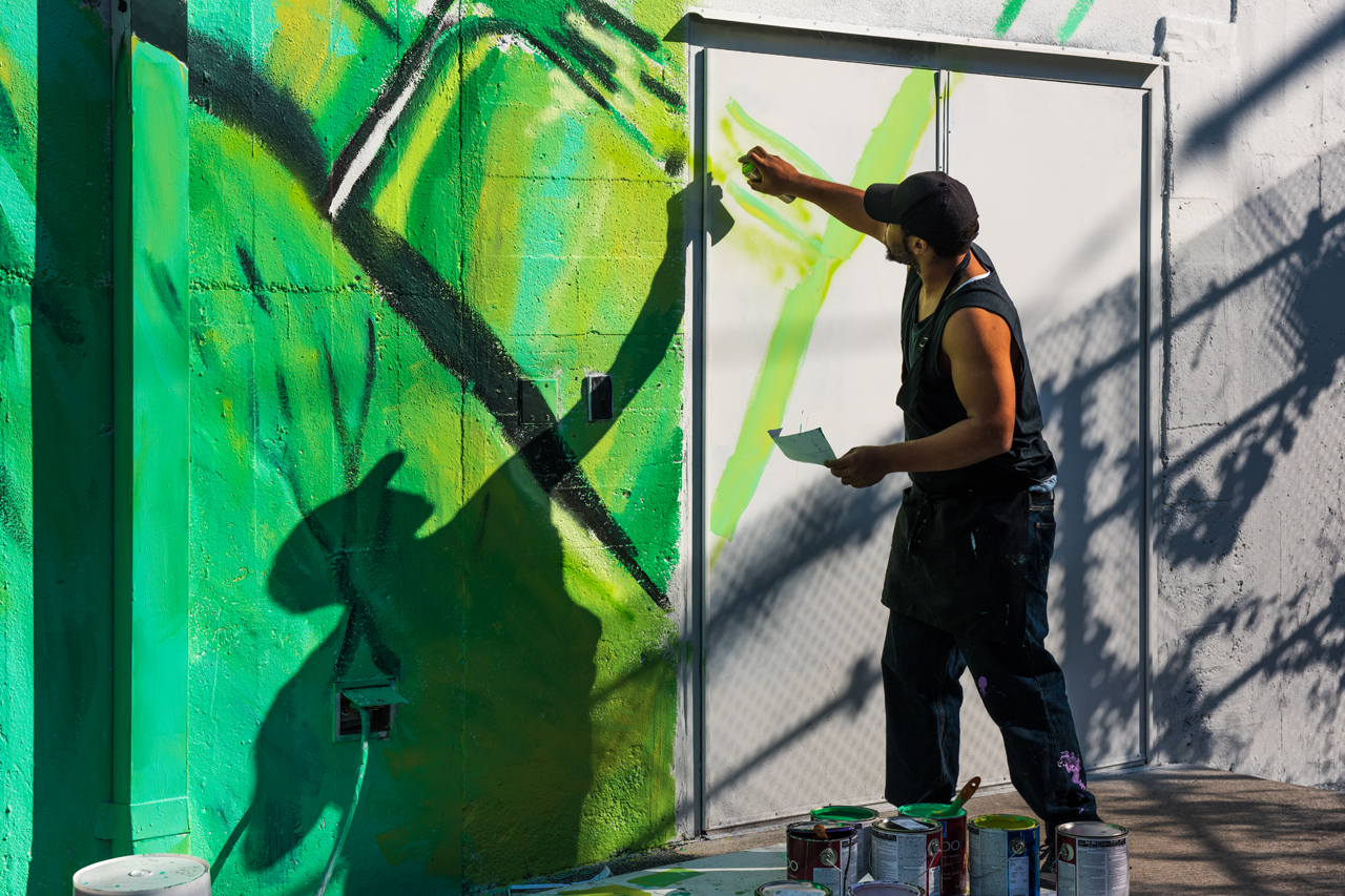 Artist Will Brown working on the right side of the mural